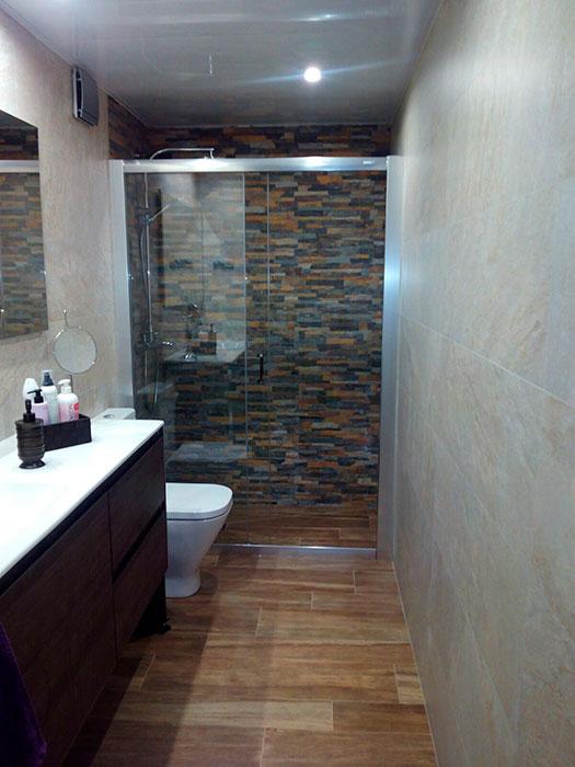 Reforma integral del baño, con plato de ducha de obra, y pared de piedra decorativa