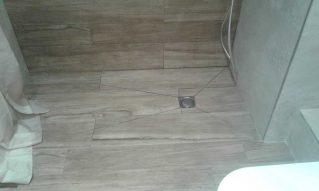 Plato de ducha de obra a medida, integrado en el baño, con el mismo suelo que la pared y suelo.
